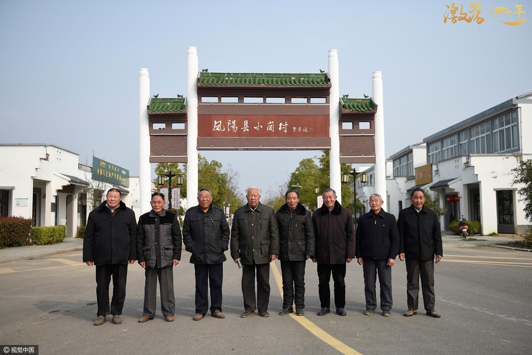 Yan Hongchang (quinto de izquierda a derecha) y otros agricultores posan frente al arco de Xiaogang.